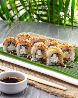 Vue latérale des rouleaux de sushi à l'anguille avec du wasabi au gingembre et de la sauce de soja sur une plaque