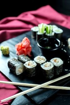 Vue latérale de rouleaux de sushi noir à l'anguille servis avec du gingembre et de la sauce de soja sur tableau noir
