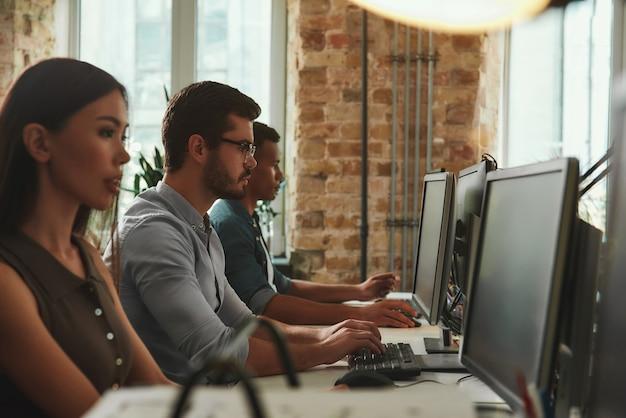 Vue latérale de routine de bureau de jeunes employés travaillant sur des ordinateurs assis dans un espace ouvert moderne