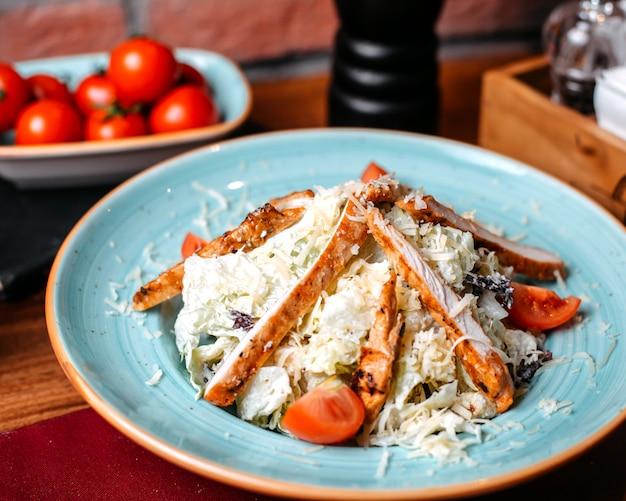 Vue latérale de la salade césar au poulet et au parmesan dans une assiette