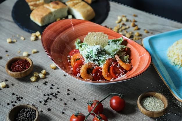 Vue latérale salade césar aux crevettes dans une assiette avec tomates et speia