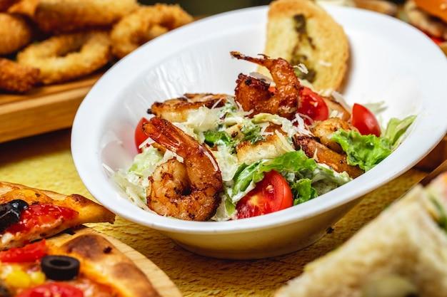 Vue latérale salade césar crevettes grillées tomate parmesan tomate et laitue
