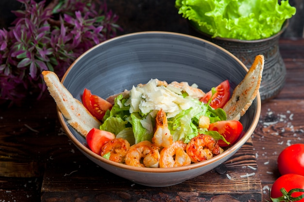 Vue latérale salade césar avec poulet et crevettes poitrines de poulet grillées, crevettes, tomates, salade fraîche dans une assiette sur une table en bois foncé