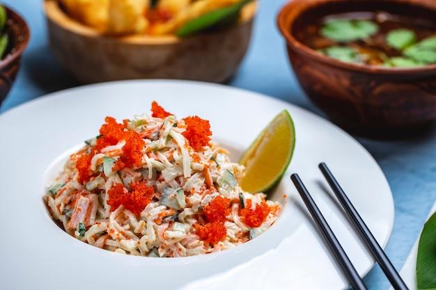 Vue latérale salade de crabe riz concombre viande de crabe tobiko mayo caviar et tranche de citron vert sur une plaque