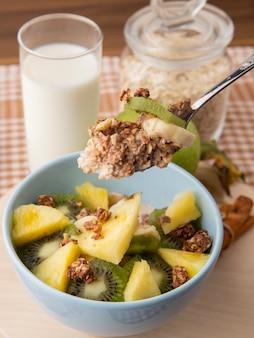 Vue latérale salade de fruits dans une assiette ananas kiwi avec granola sur une cuillère avec un verre de lait