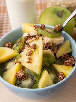 Vue latérale salade de fruits dans une assiette pomme verte ananas kiwi