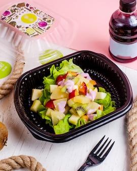 Vue latérale d'une salade de fruits avec des pommes kivi ananas et prunes servies avec du yaourt dans une boîte de livraison