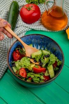 Vue latérale de la salade de légumes au concombre de tomate sur un chiffon et une table verte