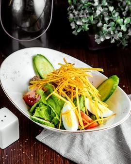 Vue latérale salade de légumes avec oeuf et oignons frits
