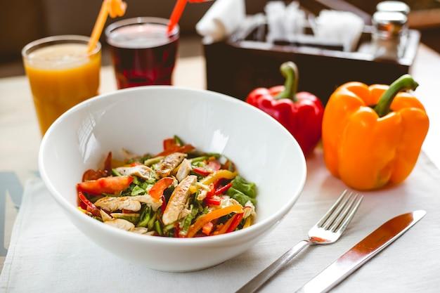 Vue latérale salade de poulet avec poivron tomate concombre laitue poulet grillé et boissons gazeuses sur la table