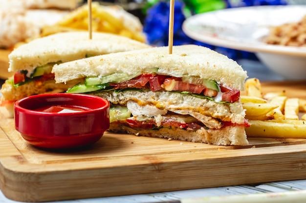 Vue latérale sandwich club avec poulet grillé tomate concombre laitue mayo ketchup et frites sur une planche