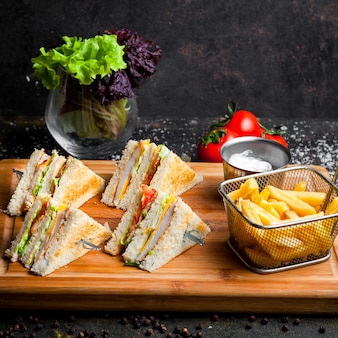 Vue latérale sandwich club avec sauce ketchup et mayonnaise et frites dans une planche de service en bois