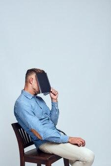 Vue latérale si fatiguée d'un homme barbu épuisé dans des vêtements décontractés couvrant le visage avec un
