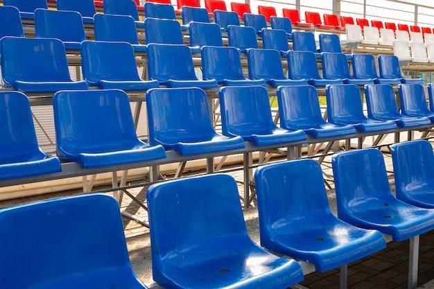 Vue latérale des sièges en plastique bleu et rouge sur la tribune du stade sportif
