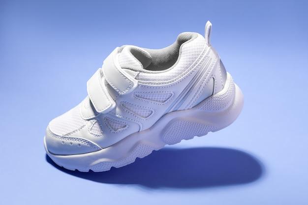 Vue latérale d'une sneaker blanche volante pour enfant avec des attaches velcro simulant une marche isolée sur un fond violet...