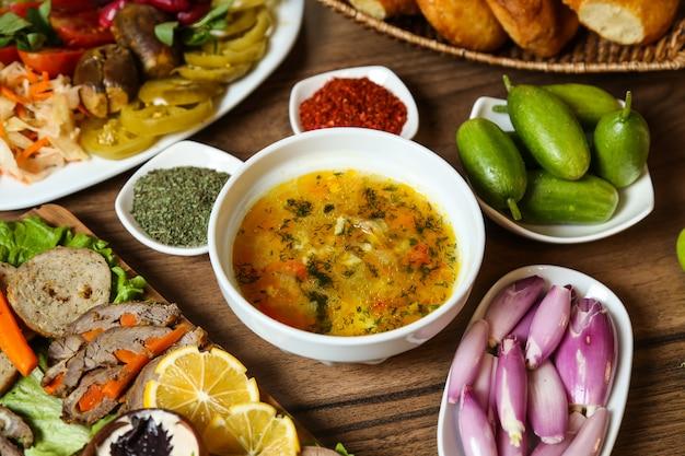 Vue latérale de la soupe au poulet avec des oignons, des concombres et des épices sur la table