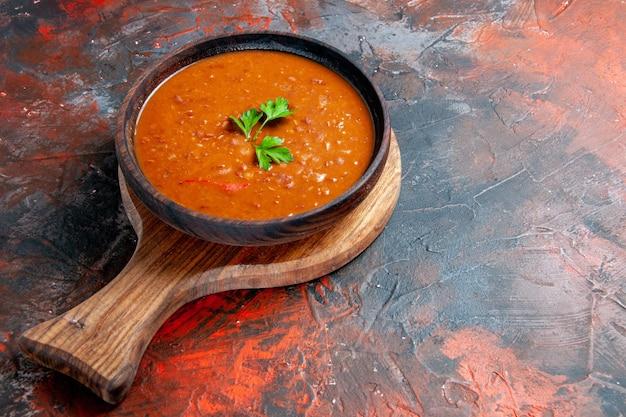Vue latérale de la soupe aux tomates sur une planche à découper brune sur le côté droit d'une table de couleurs mélangées