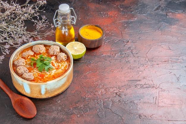 Vue latérale de la soupe de boulettes de viande avec des nouilles dans un bol marron cuillère au citron et bouteille d'huile sur une table sombre