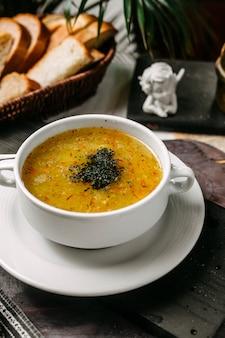Vue latérale de la soupe de pois et lentilles au safran et aux herbes dans un bol blanc