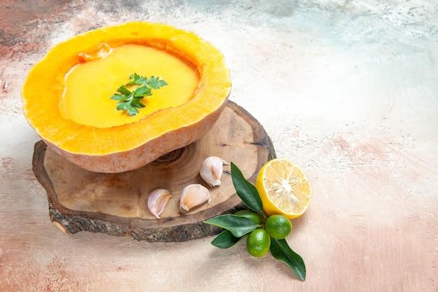 Vue latérale de la soupe de potiron soupe à l'ail sur la planche à découper à côté du citron