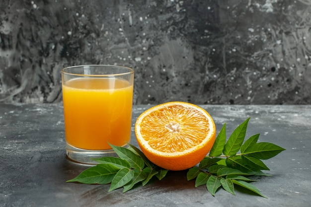 Vue latérale de la source de vitamines coupées d'oranges fraîches et de jus avec des feuilles sur fond gris