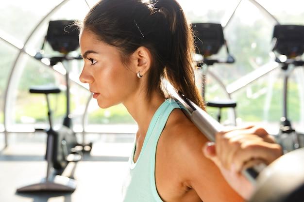 Vue latérale d'une sportive motivée faisant de l'exercice avec haltères dans une salle de sport