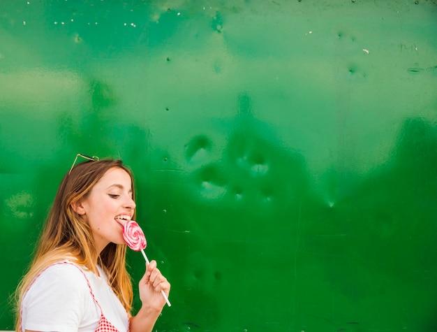 Vue latérale d'une sucette lécher une jeune femme sur fond vert