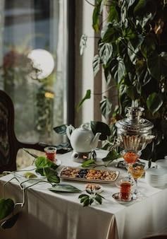 Vue latérale d'une table servie avec du thé et des noix et des fruits secs dans une assiette