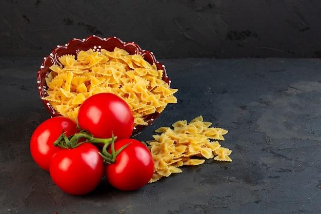 Vue latérale d'un tas de tomates fraîches avec des pâtes crues farfalle éparpillées sur fond noir