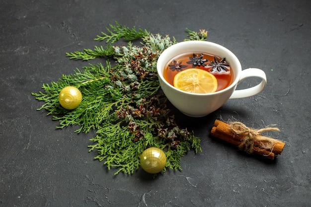 Vue latérale d'une tasse d'accessoires de thé noir et de limes à la cannelle sur fond noir