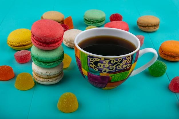 Vue latérale d'une tasse de café et de sandwichs aux biscuits sur fond bleu