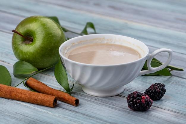 Vue latérale d'une tasse de cappuccino avec de la cannelle et de la pomme verte sur une surface grise
