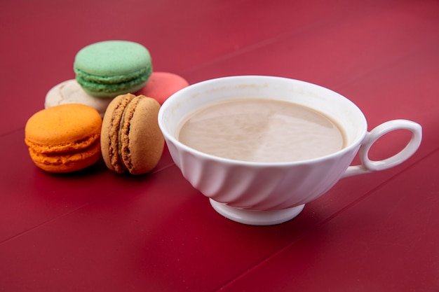 Vue latérale d'une tasse de cappuccino avec des macarons colorés sur une surface rouge