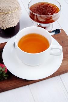 Vue latérale d'une tasse de thé avec de la confiture de fraises dans un vase en verre sur planche de bois sur blanc
