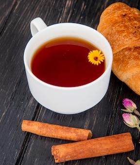 Vue latérale d'une tasse de thé avec croissant et bâtons de cannelle sur bois noir