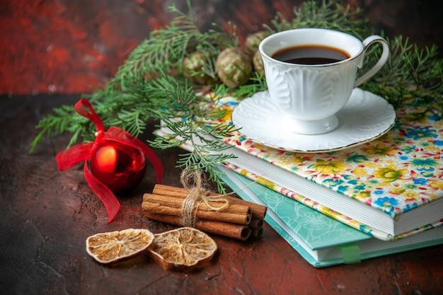 Vue latérale d'une tasse de thé noir sur deux livres, limes à la cannelle et accessoire de décoration de branches de sapin sur fond sombre