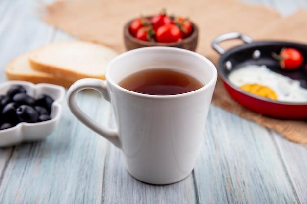 Vue latérale d'une tasse de thé avec œuf frit à la tomate sur un sac et des tranches de pain aux olives noires sur une surface en bois