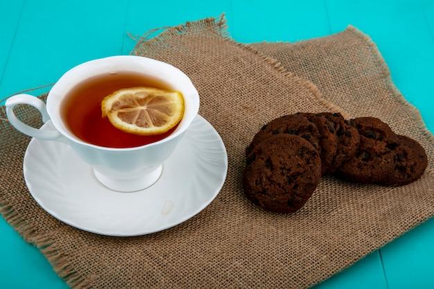 Vue latérale d'une tasse de thé sur soucoupe avec tranche de citron et biscuits sur un sac et fond bleu