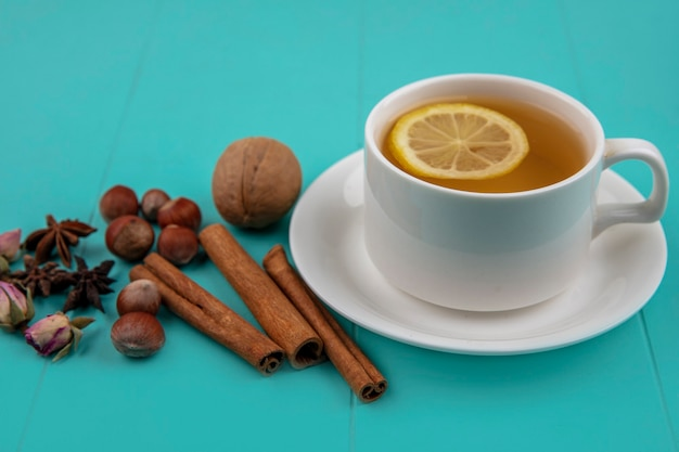 Vue latérale d'une tasse de thé avec tranche de citron et cannelle avec noix de noix et fleurs sur fond bleu