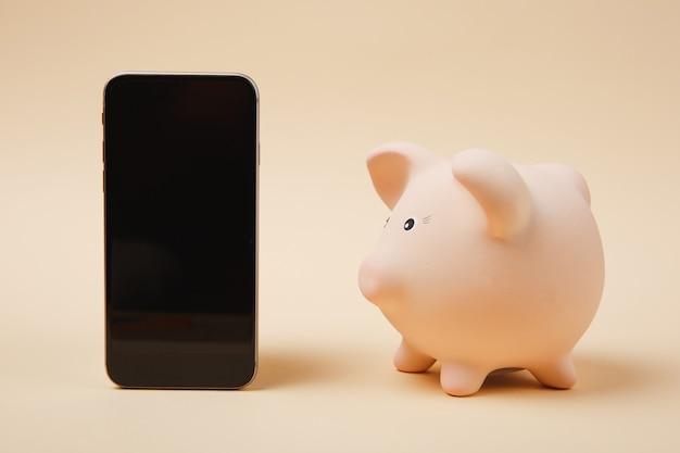 Vue latérale tirelire rose, téléphone portable avec écran vide vide isolé sur fond de mur beige. accumulation d'argent, concept de richesse des services bancaires d'investissement. copiez la maquette publicitaire de l'espace.
