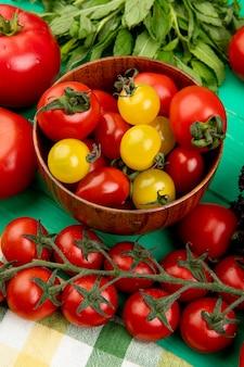 Vue latérale des tomates dans un bol avec d'autres et des feuilles de menthe verte sur table verte