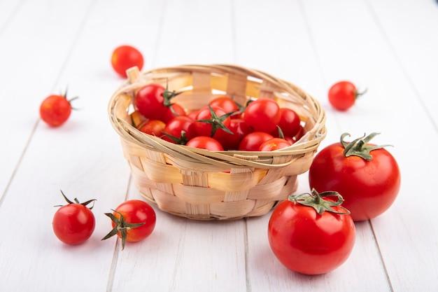 Vue latérale des tomates dans le panier et sur bois