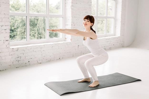Vue latérale sur toute la longueur de la belle jeune femme en tenue de sport faisant des squats en se tenant devant la fenêtre au gymnase