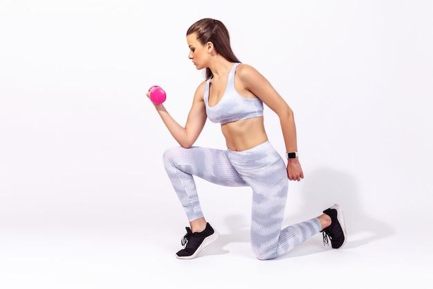 Vue latérale sur toute la longueur femme athlétique tenant des haltères à la main faisant des squats avec une jambe