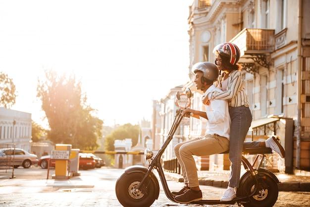 Vue latérale sur toute la longueur de l'heureux couple africain monte sur une moto moderne dans la rue