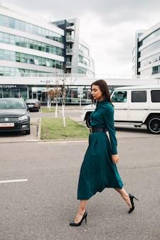 Vue latérale sur toute la longueur de la photo d'un magnifique modèle brune en robe vert foncé avec ceinture noire et talons noirs marchant le long de la route contre les bâtiments modernes de la ville.