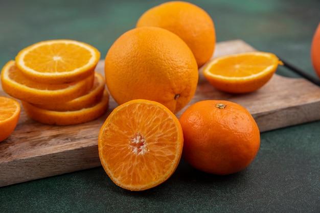 Vue latérale des tranches d'orange sur une planche à découper sur fond vert