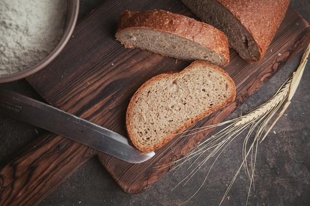 Vue latérale des tranches de pain avec un couteau sur une planche à découper et brun foncé.