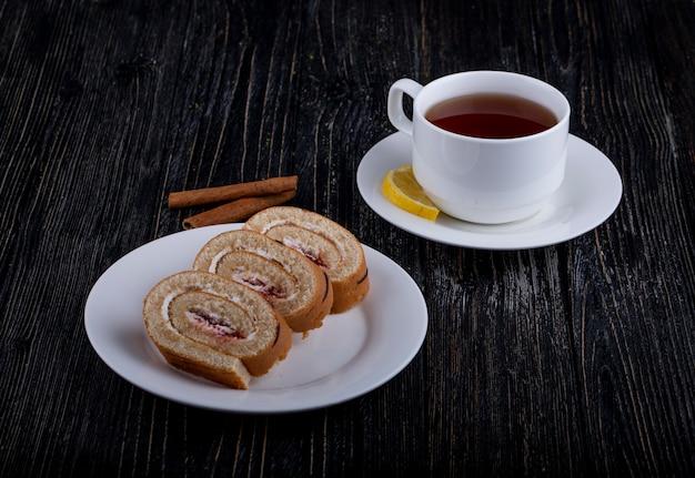 Vue latérale des tranches de rouleau suisse avec de la crème fouettée et de la confiture de framboise sur une assiette servie avec une tasse de thé sur rustique