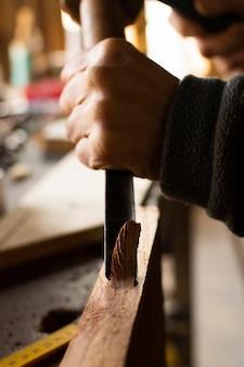 Vue latérale travaillant sur le bois avec un outil